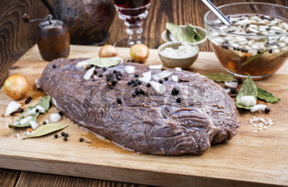 Marinated traditional German Sauerbraten from beef with onion and spice as closeup on a rustic wooden cutting board