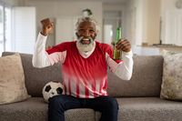 Senior man holding beer bottle cheering while watching sports on TV