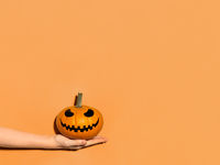Halloween pumpkin in hand on orange background.