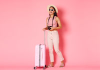Tourism, summer vacation, holidays abroad concept. Full length of carefree asian girl tourist, traveller enjoying summer resort, carry suitcase over pink background, taking pics on camera