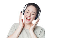 happy young woman with headphones singing along to music