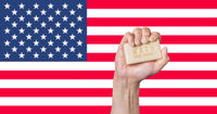 Caucasian male hand holding soap with words: Wash Your Hands against an American flag background