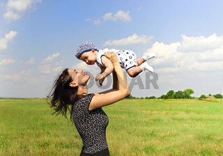 Loving mother with baby in green field