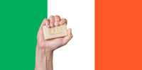 Caucasian male hand holding soap with words: Wash Your Hands against an Irish flag background