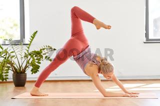 woman does downward-facing dog pose at yoga studio