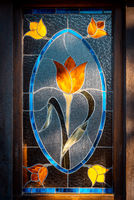 Beautiful stained glass shaping a tulip in several colours, illuminated by sun rays