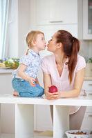 Mutter und Tochter küssen sich in der Küche