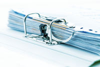 Detail of open folder filled with documents in cyan tone. Symbol of business or bureaucracy