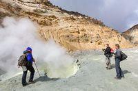 Group tourists watching eruption of hot springs, fumes fumarole, volcanic activity in crater volcano