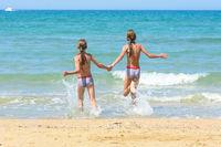 Children holding hands run swimming in the sea