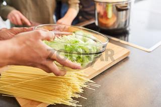 Hände beim Salat und Mittagessen vorbereiten in Küche
