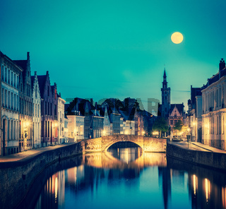 Vintage retro hipster style travel image of European medieval night city view background - Bruges (Brugge) canal in the evening