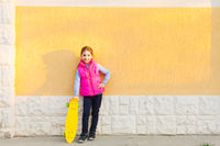 Young hipster preteen posing near wall with skateboard