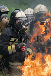 Firefighters of Fire Department Federal Fire Service in Kamchatka during fire extinguishing, training to overcome fire zone of psychological training for firefighters