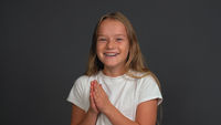 Happy charming little girl with hands put together looking a side of camera, wearing white t-shirt isolated on dark grey or black background