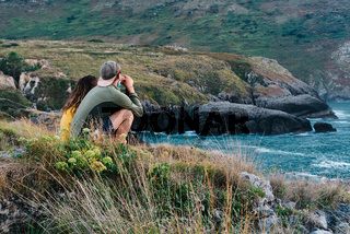 Side view of a young couple sitting on the rocks looking at the cliffs and the sea