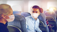 passengers in masks talking in plane