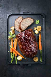 Traditional American meatloaf with ketchup from ground beef with carrots and onion as top view on a modern design cast iron tray