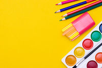 Office supplies on a yellow background. Various school supplies on a bright yellow background. Text frame with office supplies. The layout of the school. Welcome back to school. Concept of advertising office supplies.