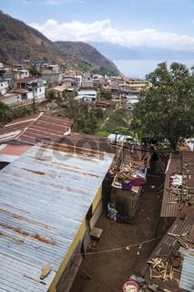 Local houses with rusty tin roofs and wood on top in mountain village along lake Atitlan, Santa Cruz la Laguna, Guatemala