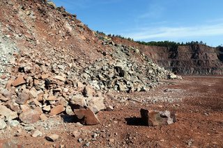 view into an open pit mine with porphyry rock material