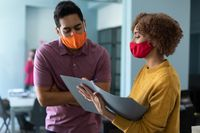 Mixed race man and woman wearing masks in an office