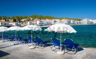 Umbrellas and beach chairs  in idyllic Greek island Spetses