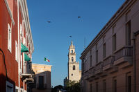 View along the colonial buildings to the tower of the cathedral of Merida, Yucatan, Mexico