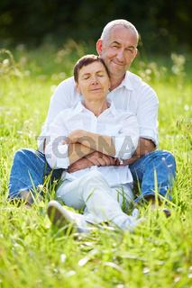 Paar Senioren sitzt entspannt auf einer Wiese