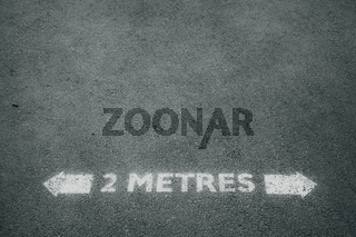 Social distancing road painted sign recommending staying 2 metres apart