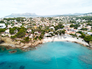 Distant view rocky coves, sandy beach, tiny bay of Benissa. Turquoise bright blue Sea waters hillside townscape at sunny day. Aerial photo drone point of view photography. Costa Blanca. Espana. Spain