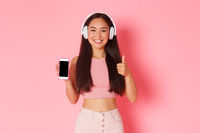 Technology, communication and online lifestyle concept. Satisfied cheerful asian girl in headphones, showing smartphone display and thumbs-up, recommend interesting podcast or singer