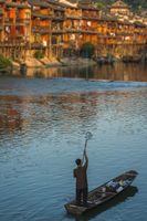 Man with small net in an old wooden boat in Fenghuang