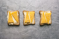 Sandwiches with butter and cheese. Morning breakfast with cheese toasts. Bread and cheese on a silver background.