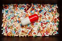 Große Pille mit bunten Medikamenten in Box
