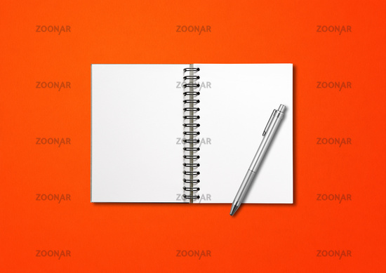 Blank open spiral notebook and pen isolated on red