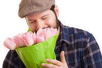 Bearded young handsome man holding a bouquet of pink tulips, smelling them with closed eyes, isolated on white background. Mothers day, Valentines day, Easter and surprise Concept.