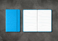 Blue closed and open lined notebooks on dark concrete background