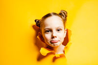 Curious little girl looking through hole in yellow paper. Seasonal sales and discounts.