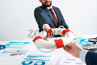 Business persons holding small lifebuoy together