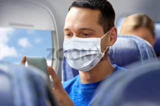 man in mask sitting in plane with smartphone