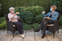 Senior woman and daughter with face masks having coffee at social disctance