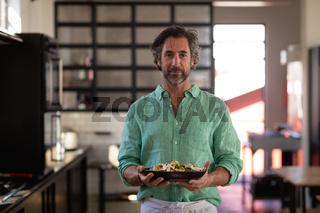 Caucasian chef showing his dish