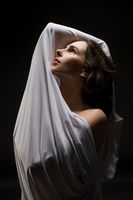 Woman wrapped in cloth outstretching arms in studio