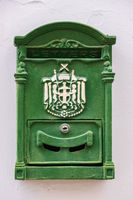 Green metal antique mailbox on a white house wall in old NIcosia, Cyprus