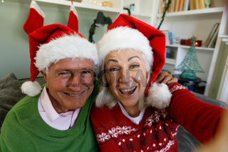Portrait of senior couple in santa hat sitting on couch and smiling looking at camera at home