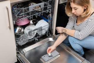 A teenager places a cube of powder in a special dishwasher monument.