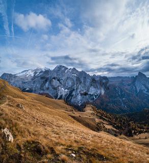 Autumn Dolomites mountain scene from hiking path betwen Pordoi Pass and Fedaia Lake, Italy. Snowy Marmolada massif and Glacier in far.