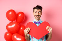 Valentines day concept. Romantic guy smiling and looking left, dreaming of date with lover, showing red big heart cutout, pink background