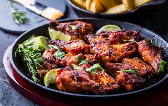 Roasted chicken wings in barbecue sauce with lime and baked potatoes in rustic pan